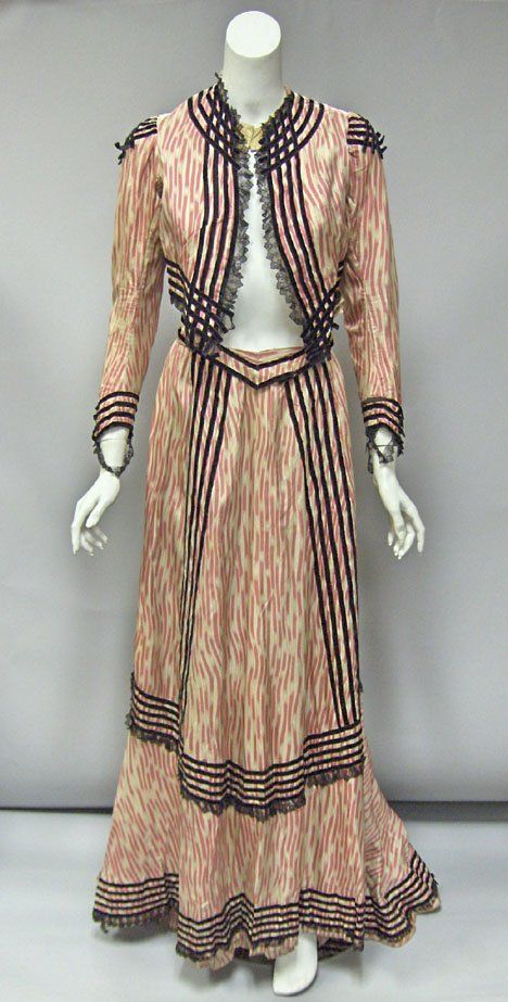 Circa 1900 Victorian pink and white printed silk velvet-trimmed dress. Bodice and skirt in fine silk printed with bright pink broken stripes, with bold black velvet striped and criss-cross patterning, black lace trim, the skirt with asymmetrical hem trailing in the back, bodice with silk chiffon shirring at waist.