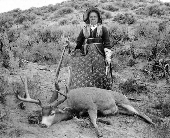 "A.G. Wallihan, photographer. Augusta Wallihan—Grocery Shopping. Albumen print, circa 1895. Standing over one of her many trophy mule deer, subsistence-and-sport huntress ""Gusty"" Wallihan appears every inch the frontier matron with her dressy bonnet, prairie-pattern cartridge belt, floral-embroidered gauntlets, hunting knife, and Remington-Hepburn rifle."