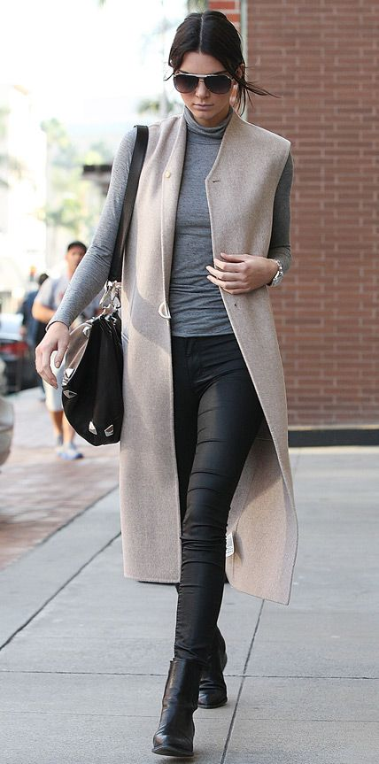InStyle.com Kendall Jenner delivers a heavy dose of off-duty style with a sleek taupe wool vest layered over a gray turtleneck knit and leather pants. A carryall and black ankle boots round out her look.