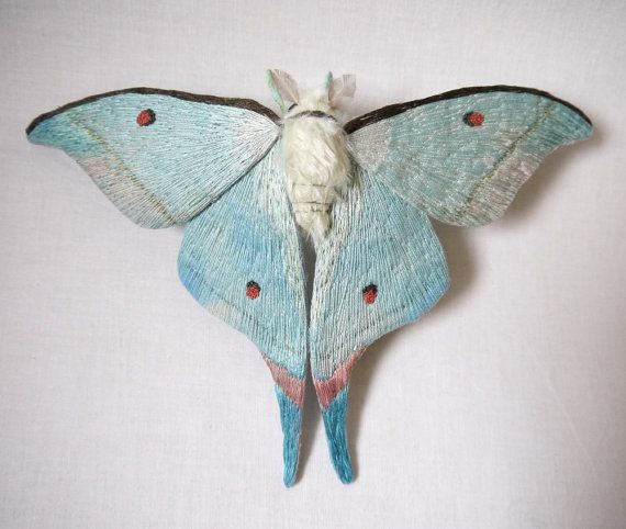 This moth is about 6 1/2 inch tall and 10 inch wide. The wings are made from cotton fabric and the body is made from fake fur. It is hand painted and