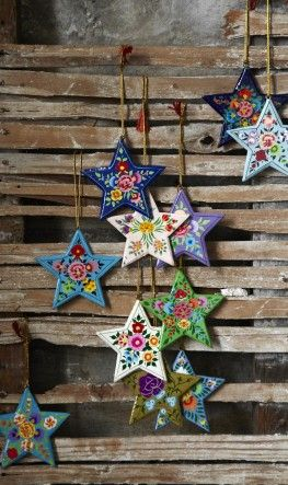 Painted wooden stars with floral motifs and a golden cord for hanging. Fairtrade.
