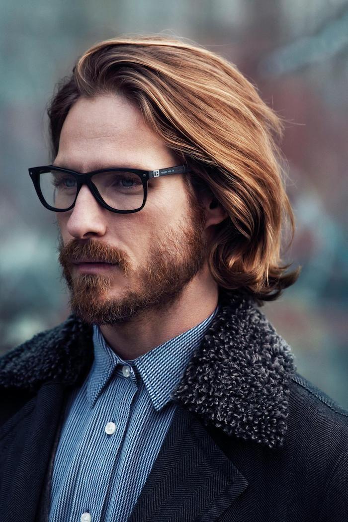 coiffure homme, chemise rayée en blanc et bleu foncé, manteau noir avec colle en faux fur, coupe de cheveux mi longs pour homme