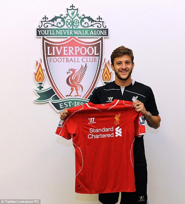 New colours: Adam Lallana poses with a Liverpool shirt at the club's Melwood training grou...