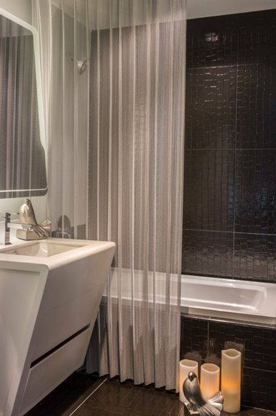small but stylish modern bathroom with black snake print tile, sheer metallic shower curtain, candles, pigeon statues... 5 Steps to Make Your Small Shower Look Bigger Without Remodeling from Bathroom Bliss by Rotator Rod