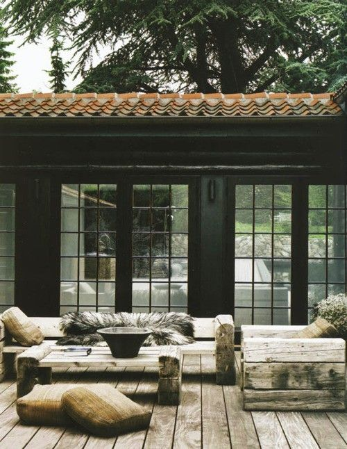 Black house exterior with deck and Spanish tiled roof
