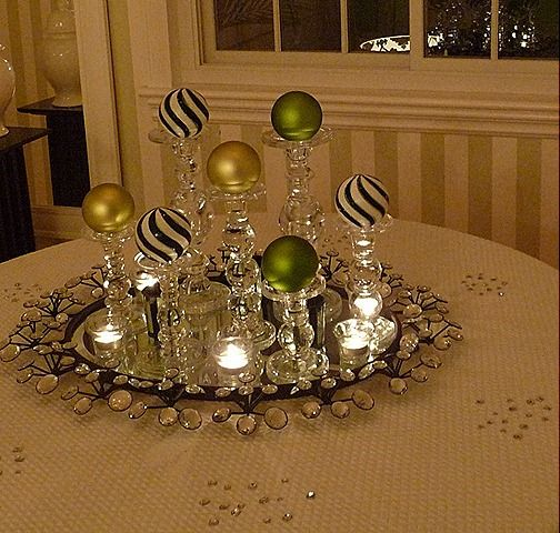 Place candle holders on a mirror top with a bulb, and add votive candles.... Beautiful display.