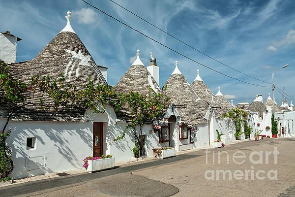 Trulli houses in the shopping street in Alberobello under a blue sky, Puglia, Italy