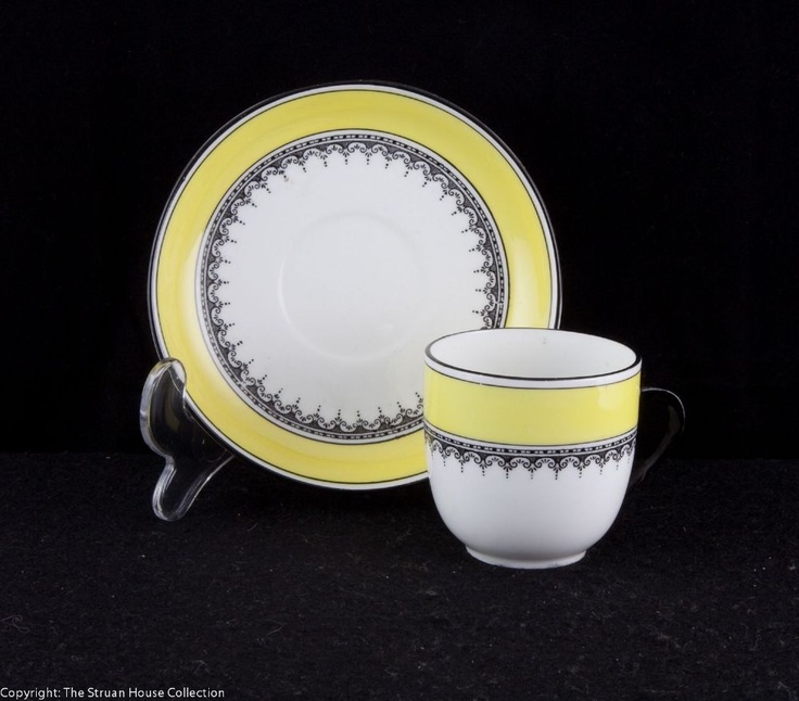 A beautifully simple coffee cup and saucer in great condition White ground decorated with lemon yellow bands and black classical frieze c1913