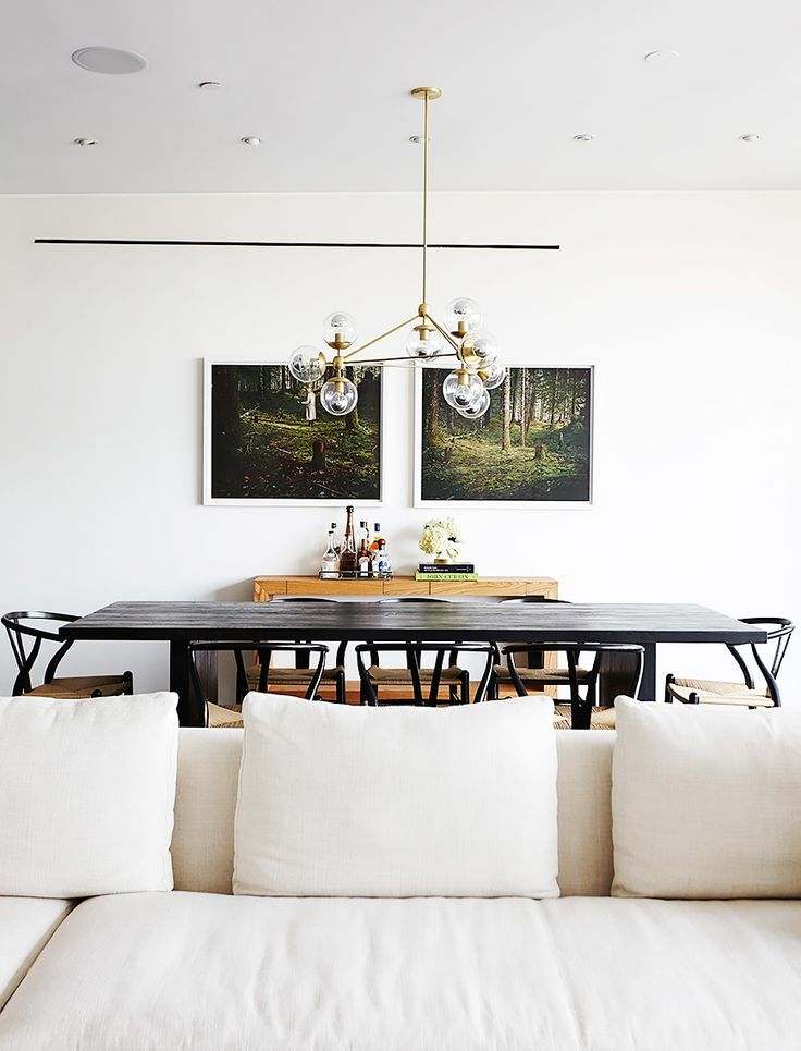 white dining room with black dining table and chairs, photography art, modern chandelier