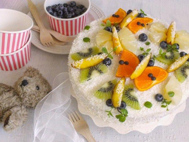 Lehký piškotový dort s krémem z mascarpone, posypaný kokosem a ozdobený ovocnými motýlky. Podrobný postup najdete na blogu.