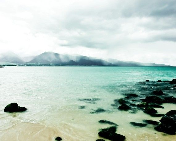 Ocean photography Beach photography aqua blue sea and rocky beach with rain on distant mountains by Lupen Grainne.