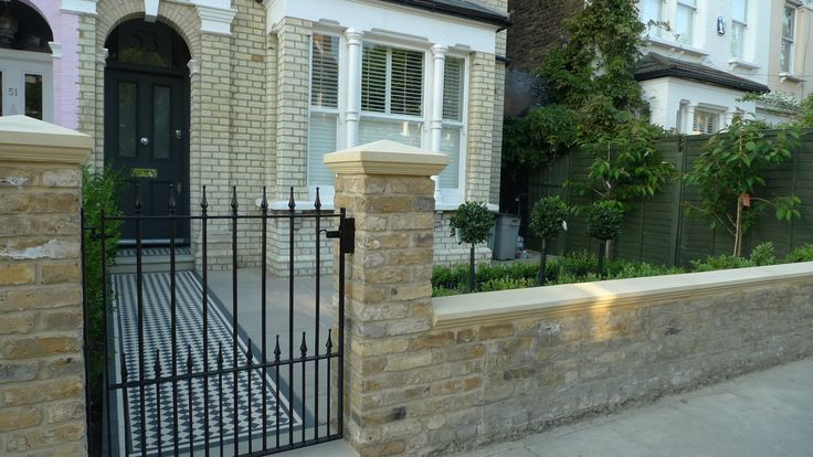 Yellow stock wall stone caps and metal front garden gate front garden London