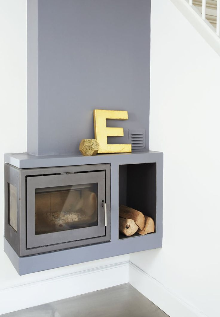 Modern fireplace in grey with counteraction from golden details.