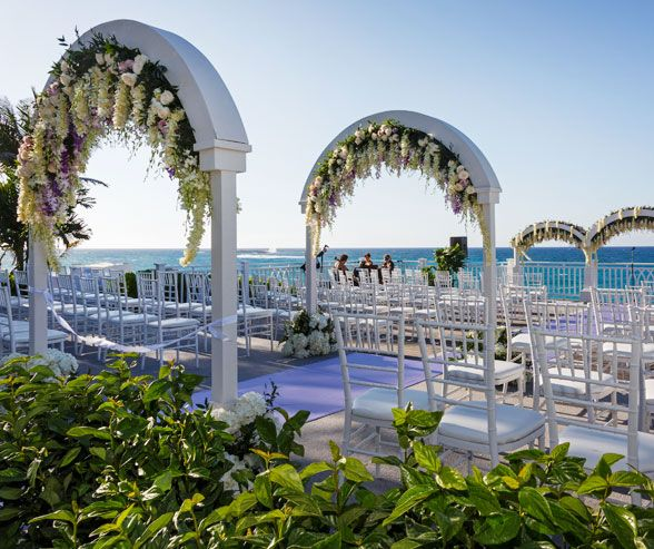 Guests are seated on traditional Chiavari chairs topped with white cushions.