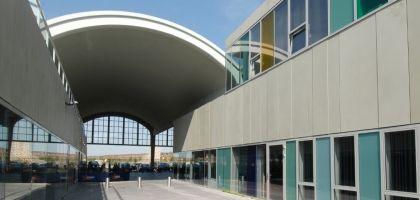 Vliegtuighangar van Welschap in Eindhoven. Horizontale banden van polyesterbetonplaten worden afgewisseld met aaneengesloten stroken glas in xzaluminium kozijnen van Reynaers B.V. Spilcentrum De Hangar