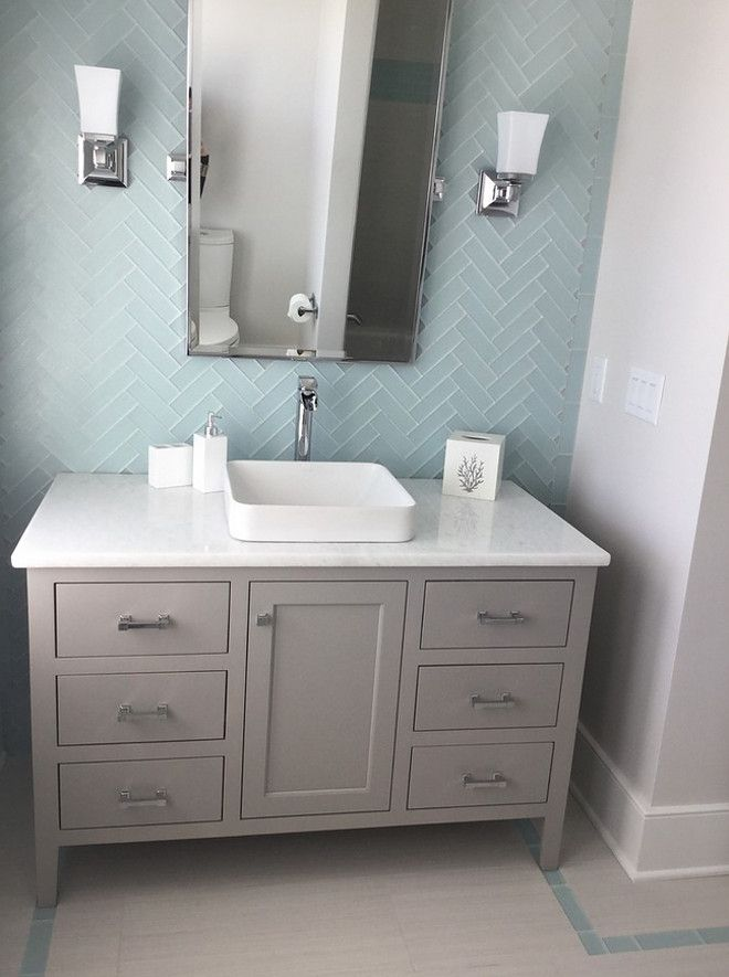 This bathroom features floor-to-ceiling subway tile in a herringbone pattern. The vanity is painted in a soft gray – Sherwin Williams SW7023 Requisite Gray.  Walls: Sherwin Williams Anew Gray & 3×6 Capricco sky blue glass tile in 3×6 herringbone pattern.  Floors: Silkwhite tile 12×24.