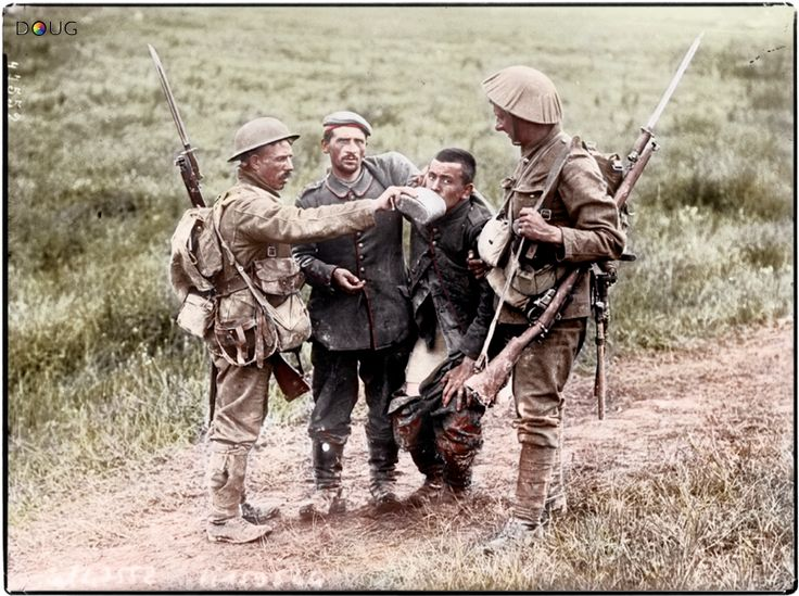 British soldiers give a drink to a wounded German soldier during the Battle of the Somme in 1916.