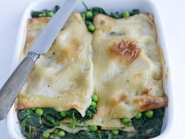 Verwarm de oven voor tot 180 ºC.  Verhit in een koekenpan de olijfolie. Fruit de knoflook. Voeg de spinazie in porties toe en laat al omscheppend slinken en het vocht verdampen.Bak de erwten 2 min. mee. Neem de pan van het vuur en breng op smaak met zout en peper.  Bestrijk de bodem van de ovenschaal met een dun laagje saus. Dek af met lasagnebladen en verdeel er een laag groenten over. Verdeel er 2 lepels saus over. Bestrooi met zout en peper. Maak met de rest van de lasagnebladen…