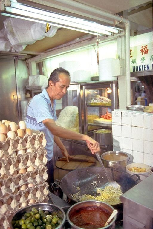 A HAWKER FRYING HOKKIEN MEE (C.1980S). Photo credit: Singapore Tourist Promotion Board Collection/NAS