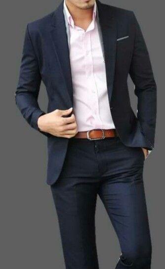 Él lleva un traje azul marino con una camisa rosada.
