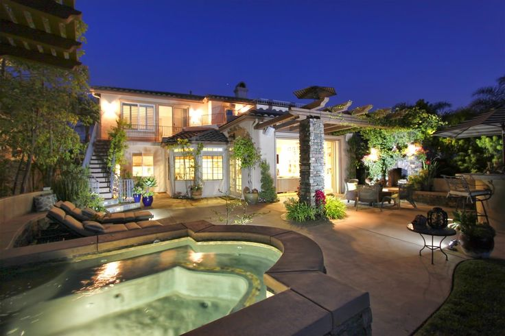 Mediterranean Hot Tub with Palm trees, Built-in concrete seating, Hot-tub, Exterior stone fireplace, Outdoor kitchen, Fence