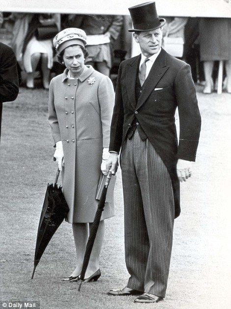 1966: Racing again - this time preparing for inclement weather as the royal couple clutch their umbrellas at the Epsom Derby (seemingly before the Queen's passion for her transparent umbrellas began)