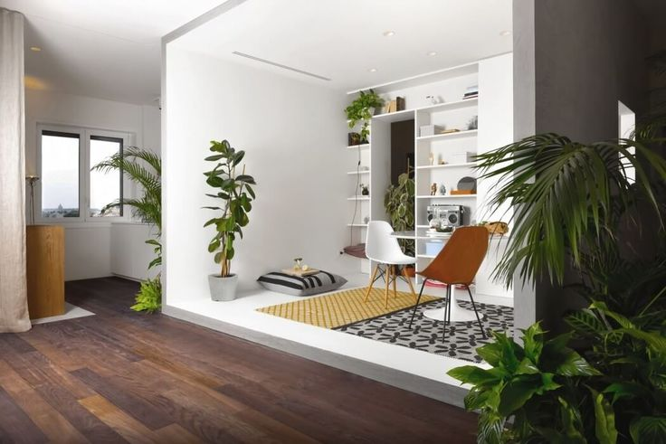 This plant-filled apartment in Milan was developed around a white concrete box, aliving roomthat's framed in and closed on three sides.