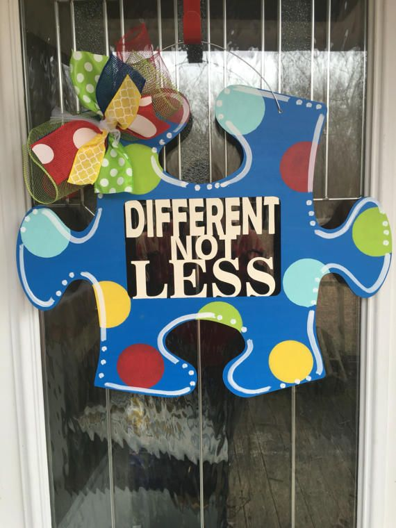 This door hanger is made from 1/4 in wood and measures 22.5x19 inches. It is hand painted. The words different not less are in the center. We could also put a name or other saying in the center. We add a wire hanger and a colorful bow.