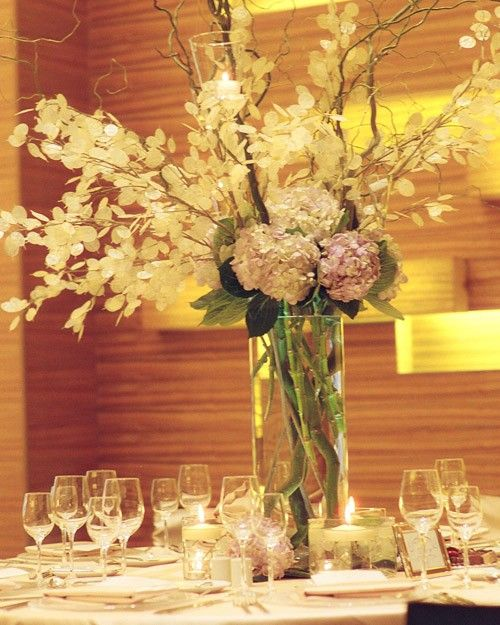 Hydrangea and lunaria spill out of this tall centerpiece