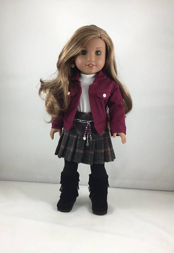 This adorable ensemble has a jean jacket with lots and lots of detailing and top-stitching. The fabric is a burgundy denim. It has 2 faux front pockets with silver metal buttons. The sleeves have cuffs closed by snaps also accented with the silver buttons. The back has two flaps on