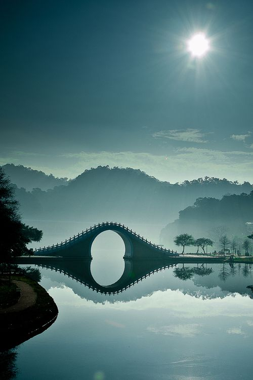 Stunning photo...The main focus of each marvelous image is the area around the Moon Bridge in Taipei, Taiwan. The soft blue, monochromatic palette and the sparkling rays of sunshine make the images feel so peaceful. The crystal clear water allows for a perfect reflection of an upside down world and his tones, lighting, and composition are exceptional.    viaMy Modern Metropolis.    new favourite, omg