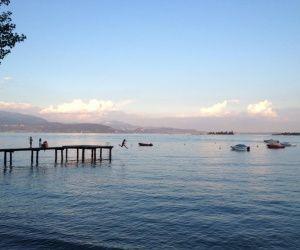 Tauchen Sie ein in kristallklares Wasser am campingplatzeigenen Strand am Gardasee.