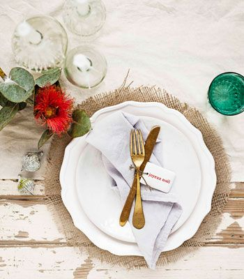 Outback glamour. To anchor each place setting, we cut out hessian circles to use as placemats. The traditional dinner plate looks as regal as a charger plate, while the brass cutlery tied with a porcelain Christmas tag adds to the sense of occasion. When it comes to flowers, only Australian natives will do, with glassware in eucalyptus green to tie the look together.