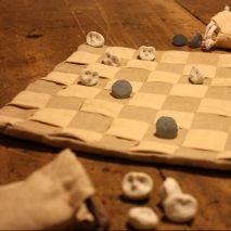 """PLAY CHEQUER WITH OWLS Questa scacchiera d'ispirazione nordica è realizzata artigianalmente a partire da due differenti qualità di pregiato lino intrecciato e cucito a creare una macrotessitura. Le pedine sono piccoli gufi notturni, realizzati a mano in porcellana e possono essere riposte all'interno della """"fodera"""", che si trasforma a piacimento in cuscinetto da viaggio."""