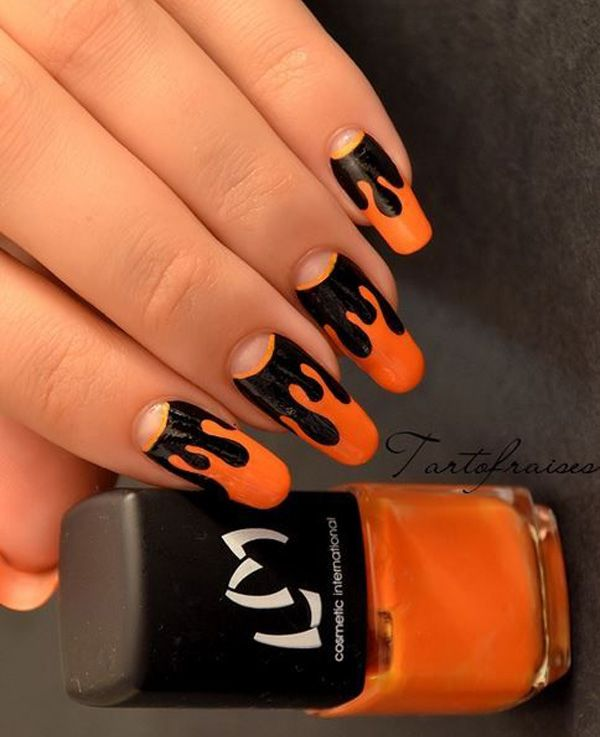 Dripping pumpkin juice inspired Halloween nail art. Coat your nails in black and orange polish to depict the dripping pumpkin juice on the tip of your nails.