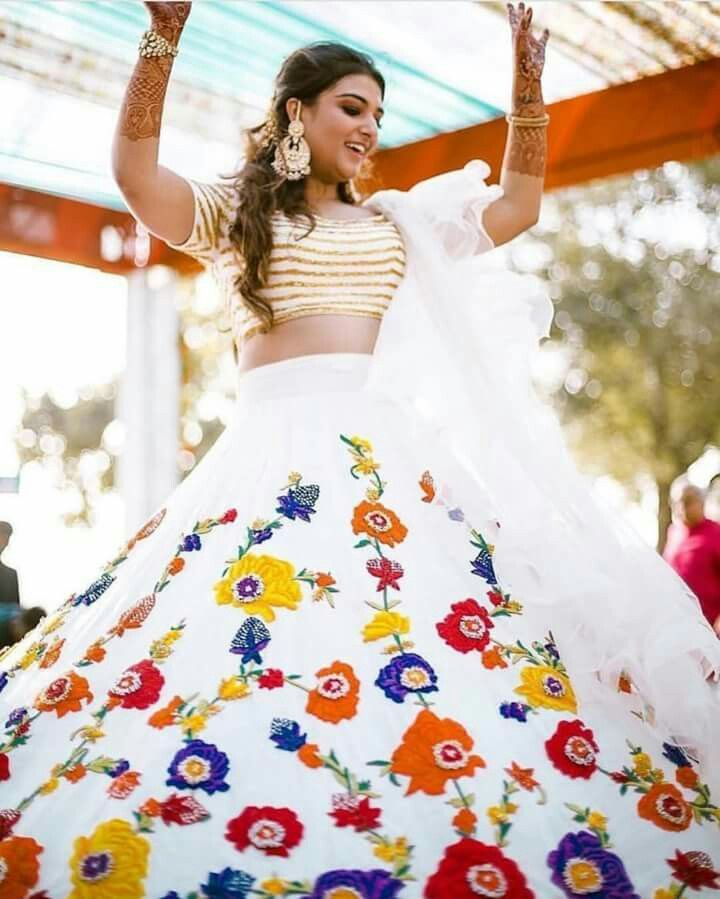 0f080c88d6 Perfect lehenga for haldi and mehendi ceremonies Ivory lehenga with gold  detailing on blouse and multi colour flowers on skirt