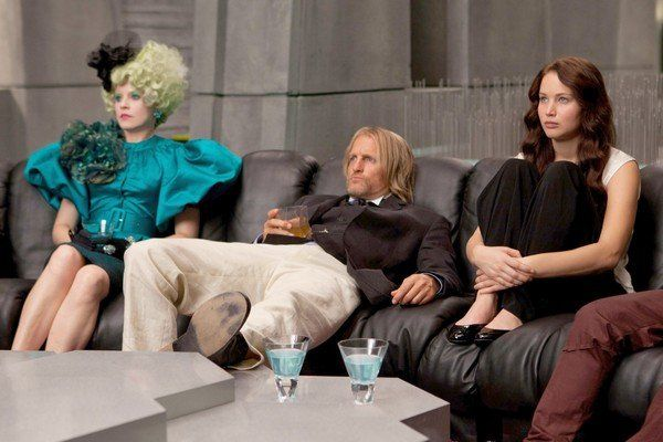 Elizabeth Banks as Effie Trinket, Woody Harrelson as Haymitch Abernathy, and Jennifer Lawrence as Katniss Everdeen in The Hunger Games.