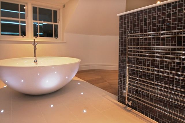 Mini ground lights mark the way to this free standing egg bath in a unique octagonal his and hers ensuite