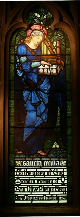 St Cecilia, with her symbolic attribute, a portable organ/musical instrument, as portrayed (in stained glass) by Sir Edward Burne-Jones.