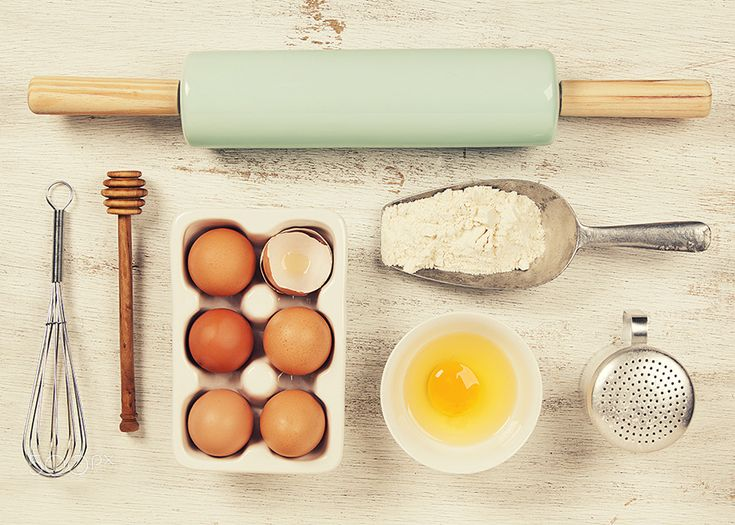 Baking concept - Baking tools and ingredients - flour, rolling pin, eggs, measuring spoons on vintage wood table. Top view. Rustic background with free text space