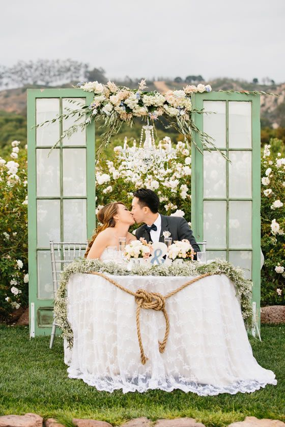 Gorgeous sweetheart table set up! Vintage shutters linked by an overhead floral arrangement and crystal chandelier.