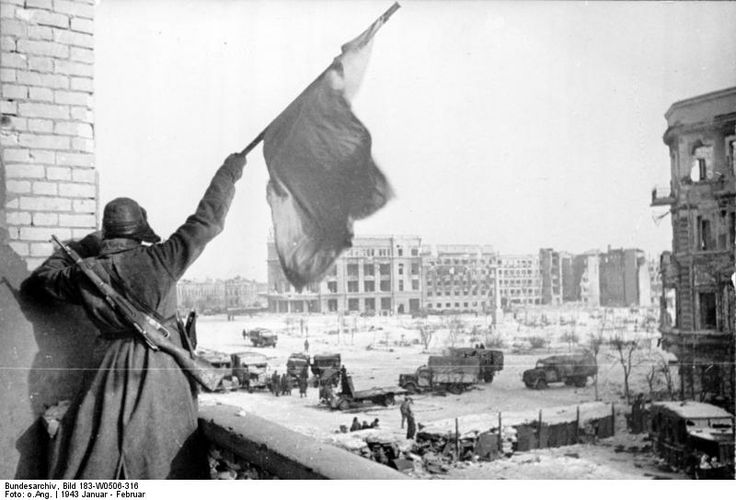 Russian soldier waving a red flag at a building off the central square in Stalingrad, Russia, Jan-Feb 1943.