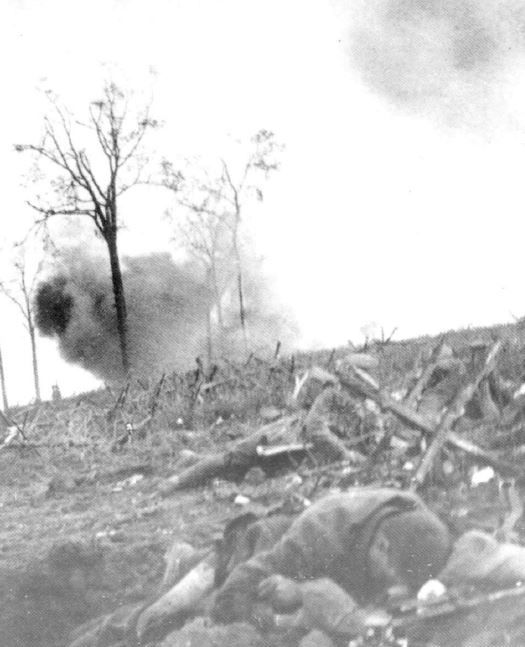 A shell explodes close to British troops at Y Wood near Hooge, in the Ypres Salient. 16 June 915.