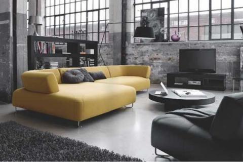 Желтый диван на фоне темно-серых стен