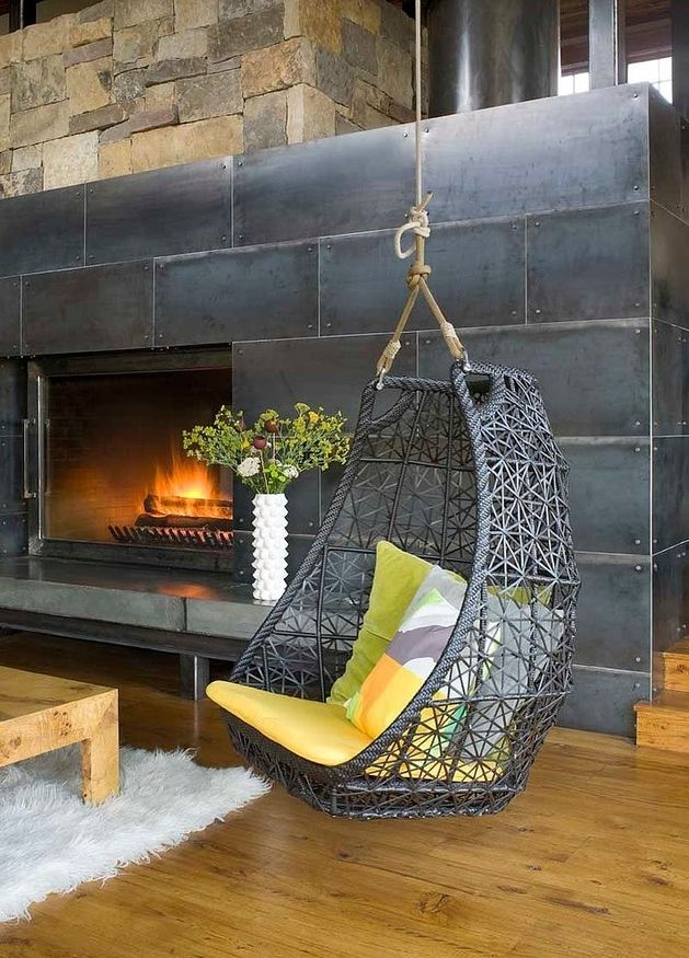 Bamboo hanging chair sprayed to match the finish of aged steel, situated next to a blazing fireplace.