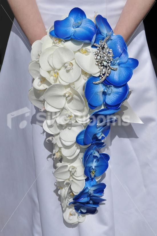 This ivory and blue cascading bridal bouquet is made with realistic phalaenopsis orchids. Made in an cascading design this artificial bouquet would suit any bride. The beautiful brides wedding bouquet is finished off with a sparkling clear crystal brooch and the handle is tied of with a premium quality ivory satin ribbon with ivory ribbon bow and crystals.
