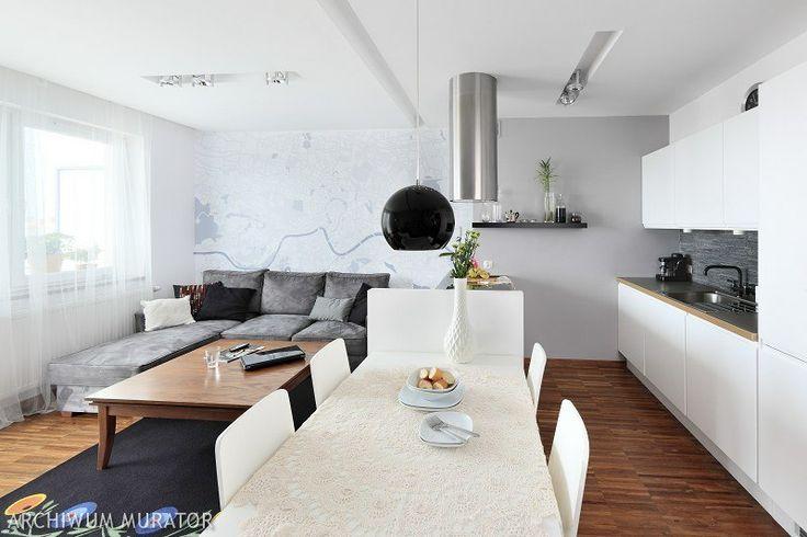 Mimo że nie ma tu wielu dizajnerskich przedmiotów, salon z kuchnią prezentuje się nowocześnie. Nie brakuje mu również przytulności. Bo białej kuchni właścicielka wybrała szary kolor ścian w salonie. Szary ze wszystkim dobrze się komponuje, dlatego polecamy go w aranżacji wnętrz. Szare ściany w połączeniu z czernią są eleganckie i stylowe, a w otoczeniu bieli subtelnieją. Ponadto wnętrza w kolorze szarym łatwo ożywić inną barwą. Jedną ze ścian salonu zdobi ...