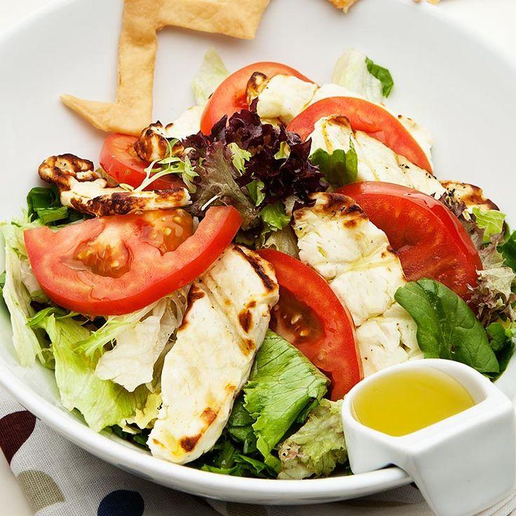 Taze marul yaprakları üzerinde, domates, roka ve hellim ızgara, zeytinyağı ve limon sosu ile
