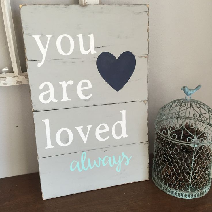 14X22 You Are Loved Distressed Sign, baby shower guestbook, mother's day gift idea. This is a beautiful piece that would make a great gift or would be great in your home. This would look great in a nursery also.This sign is hand painted and distressed. You can choose a different background color. This one is country gray and white. You can also choose a different accent color, the accent word in the sample is mint, and a different heart color which is navy blue in the sample picture. This...