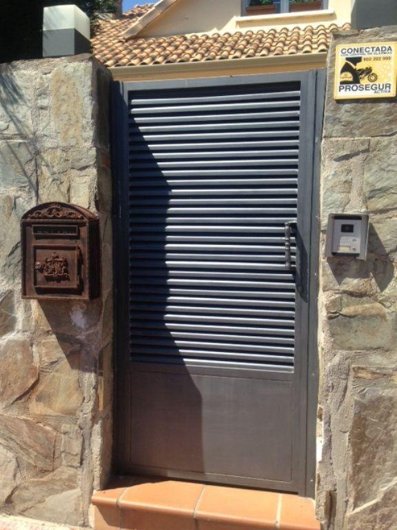 puerta peatonal de hierro con perfiles de lama z colocados en horizontal y zcalo de chapa